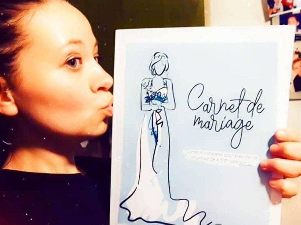 Amélie tenant son carnet de mariage comme un trésor qui contient le rétroplanning de l'organisation du mariage
